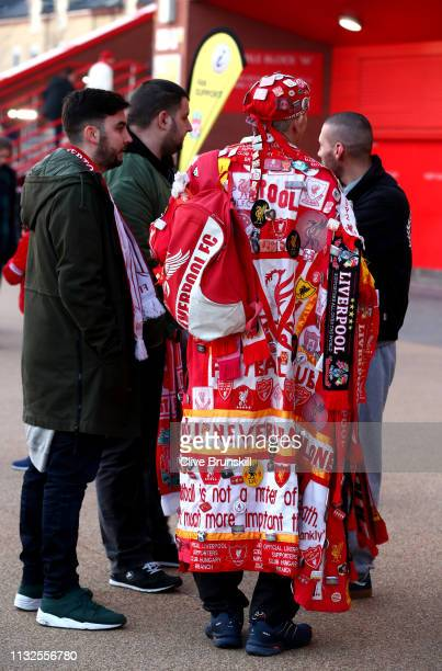 Liverpool fan is seen wearing a flag and badges outside the stadium prior to the Premier League match between Liverpool FC and Watford FC at Anfield...