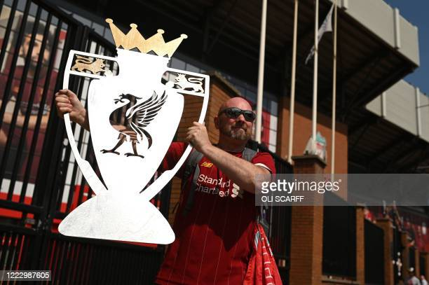 Liverpool fan Paul Davies poses with a cut out of a trophy outside Anfield stadium in Liverpool, north west England on June 26, 2020 after Liverpool...