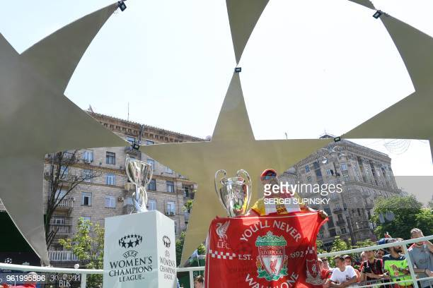 A Liverpool fan reacts as he poses next to the UEFA Champions League Cup and the Women's Champions League Cup on display at the fan zone in Kiev on...