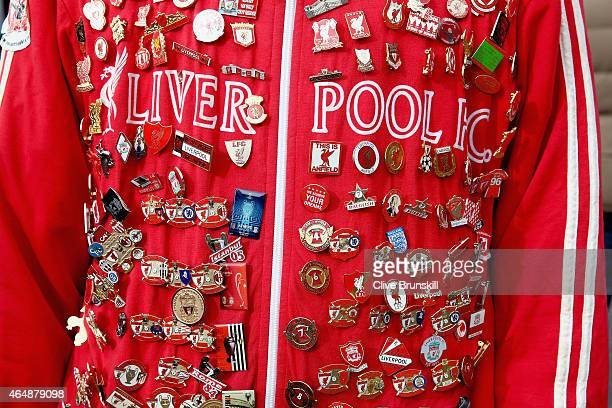 Liverpool fan shows off his pin badge collection on his track suit top prior to the Barclays Premier League match between Liverpool and Manchester...