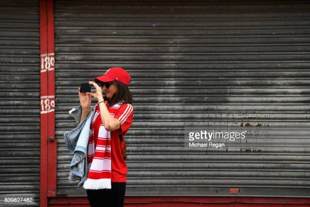 Liverpool fan takes a photo outside the stadium prior to the Premier League match between Liverpool and Arsenal at Anfield on August 27 2017 in...