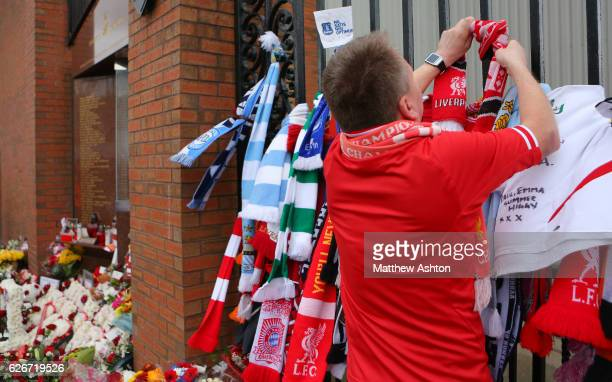 A Liverpool fan ties a scarf to the Shankly Gates alongside the Hillsborough memorial outside Anfield stadium the home of Liverpool Football Club