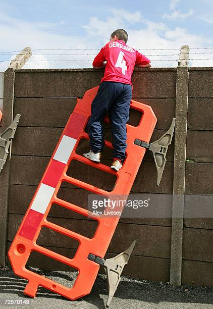 Liverpool fan uses a roadwork barrier to get a glimpse of the Liverpool team training session ahead of the Champions League Semi Final Second Leg...