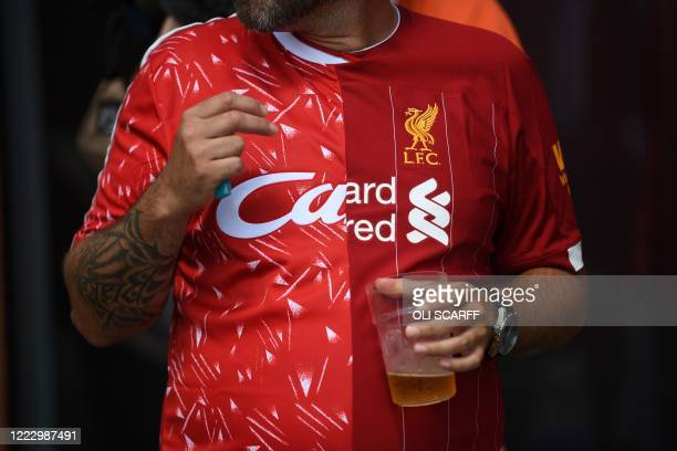 A Liverpool fan wears a halfanhalf Liverpool shirt featuring 1990 and 2020 symbolising the 30 years between Premier League victories as he drinks a...