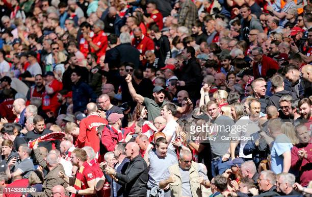 Liverpool fans celebrate after hearing Manchester City were a goal down at Brighton early in the first half during the Premier League match between...
