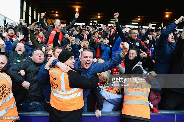 Liverpool fans celebrate as Christian Benteke of Liverpool scores the second goal from the penalty spot during the Barclays Premier League match...