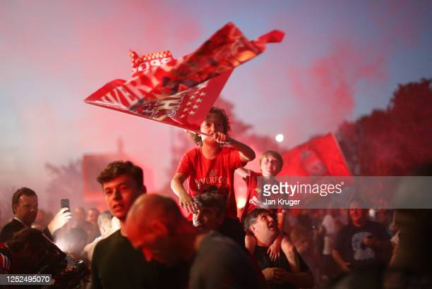 Liverpool fans celebrate as their team clinches the Premier League title at Anfield on June 25, 2020 in Liverpool, England. Liverpool are crowned...