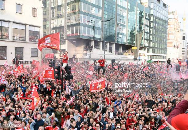 Liverpool fans celebrate as they watch the UEFA Champions League victory parade after their team won yesterday's final against Tottenham Hotspur in...