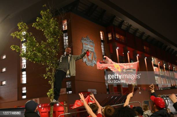 Liverpool fans celebrate outside Anfield in Liverpool, north west England on July 22, 2020 after Liverpool's final home English Premier League...