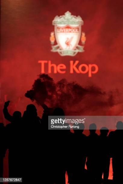 Liverpool fans celebrate outside Anfield stadium as Liverpool lift the Premier League trophy after their match against Chelsea on July 22 2020 in...