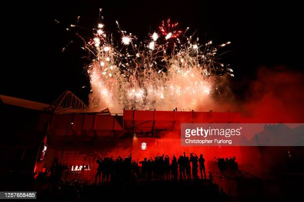 Liverpool fans celebrate outside Anfield stadium in front of fireworks from inside the stadium as Liverpool lift the Premier League trophy after...