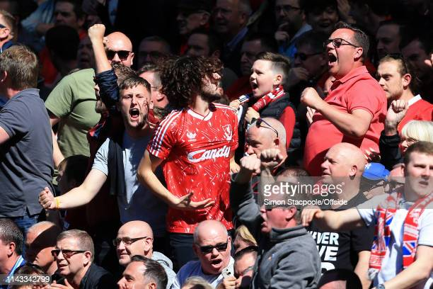 Liverpool fans celebrate the news of Brighton Hove Albion's 1st goal against Manchester City during the Premier League match between Liverpool and...