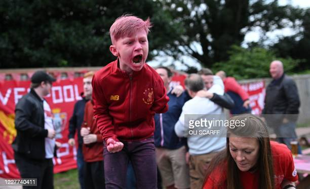 Liverpool fans celebrates their team's third goal as they watch a big screen showing Liverpool's final home English Premier League football match of...