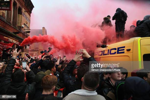 Liverpool fans climb on the roof of a police van as they set off red flares to welcome the team bus outside The Arkles pub ahead of during the UEFA...