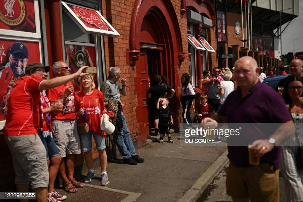 Liverpool fans drink takeaway draught beer in plastic cups outside The Albert pub, opposite Anfield stadium in Liverpool, north west England on June...