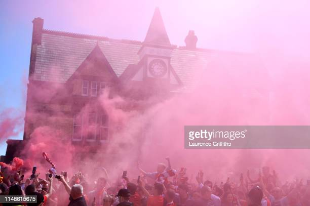 Liverpool fans enjoy the pre match atmosphere as flares are seen outside the stadium prior to the Premier League match between Liverpool FC and...