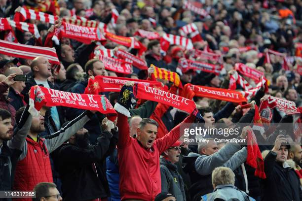 Liverpool fans hold scarves aloft as they show their support ahead of kickoff during the UEFA Champions League Semi Final second leg match between...