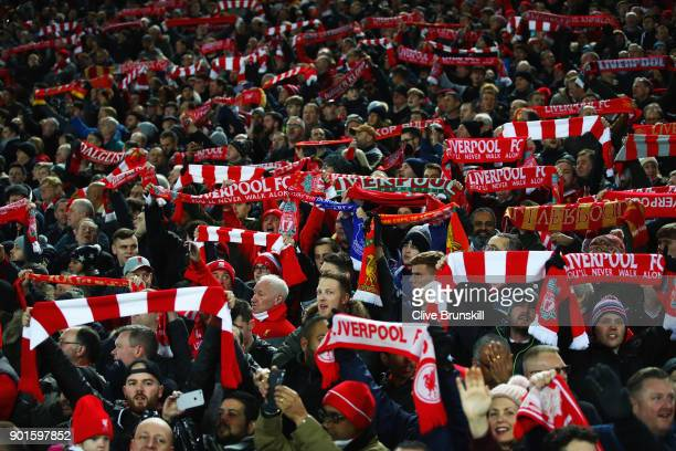 Liverpool fans hold scarves prior to the Emirates FA Cup Third Round match between Liverpool and Everton at Anfield on January 5 2018 in Liverpool...