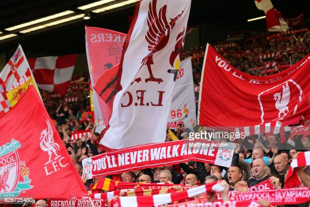 Liverpool fans hold up flags and banners on The Kop at Anfield Stadium with a flag of YOU'LL NEVER WALK ALONE