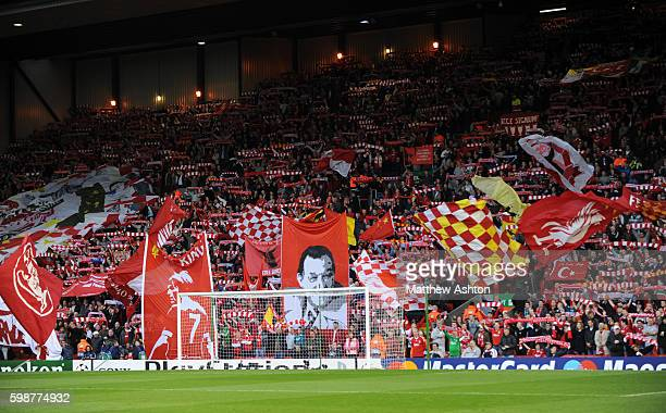 Liverpool fans hold up scarves and wave flags as they sing You'll Never Walk Alone on The Kop at Anfield Stadium