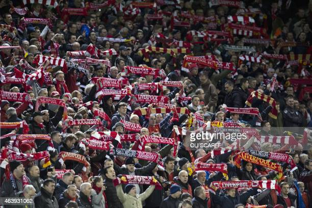 Liverpool fans hold up their football scarves and sing 'You'll Never Walk Alone' before the UEFA Europa League round of 32 football match between...