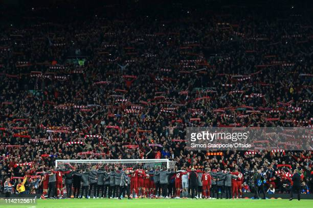 Liverpool fans in The Kop hold their scarves aloft as their players celebrate their victory after the UEFA Champions League Semi Final second leg...