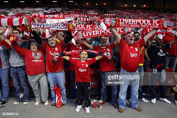 Liverpool fans in The Kop singing and holding up their scarves before the UEFA Champions League Third Qualifying Round match between Liverpool and...