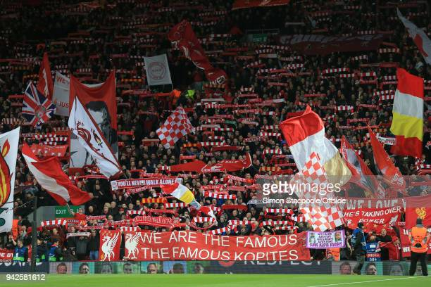 Liverpool fans in The Kop wave flags and banners and hold their scarves aloft during the UEFA Champions League Quarter Final First Leg match between...