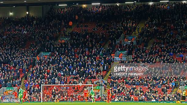 Liverpool fans leave the stands at the Kop End after 77 minutes' of play during the English Premier League football match between Liverpool and...