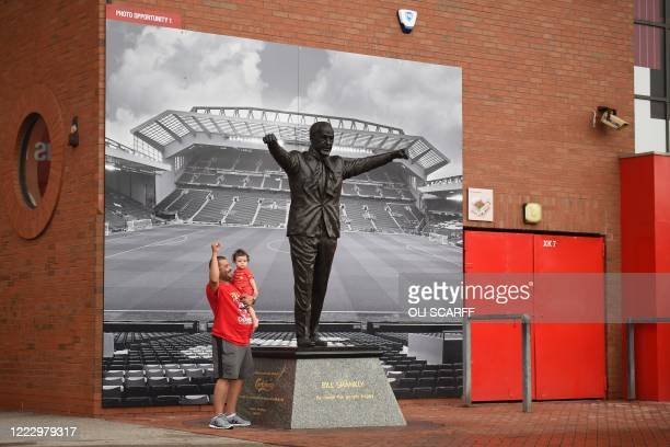 Liverpool fans pose for a photograph beside the statue of former manager Bill Shankly as supporters celebrate Liverpool sealing the Premier League...