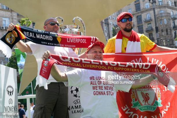 Liverpool fans pose in front of the UEFA Champions League Cup on display at the fan zone in Kiev on May 24 ahead of the football match between Real...