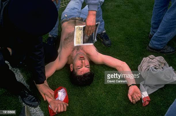 Liverpool fans pulse is checked as he lies on the ground before the Football Association Cup Semi-Final match between Liverpool and Nottingham Forest...