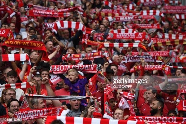 Liverpool fans raise their scarves in the crowd ahead of the English Premier League football match between Liverpool and West Ham United at Anfield...