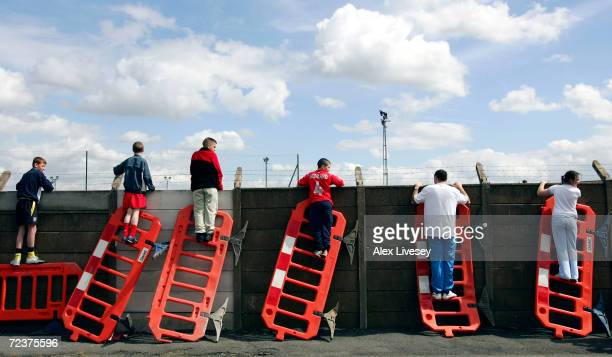 Liverpool fans use roadworks barriers to get a glimpse of the Liverpool team training session ahead of the Champions League Semi Final Second Leg...