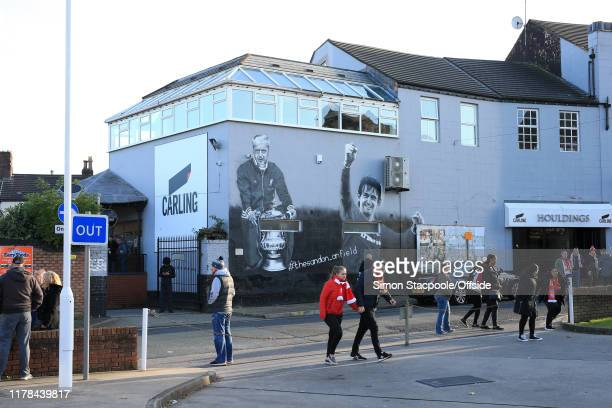 Liverpool fans walk past a mural of former Liverpool managers Bill Shankly and Kenny Dalglish en route to the Premier League match between Liverpool...