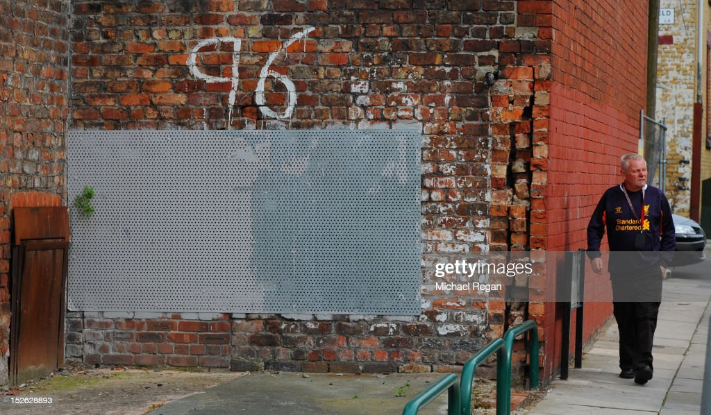 A Liverpool fans walks by a tribute to the 96 victims of the Hillsborough disaster during the Barclays Premier League match between Liverpool and Manchester United at Anfield on September 23, 2012 in Liverpool, England.