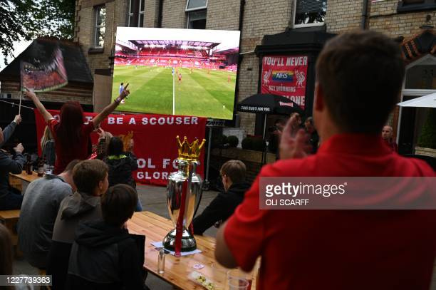 Liverpool fans watch a big screen in a beer garden showing Liverpool's final home English Premier League football match of the season against Chelsea...