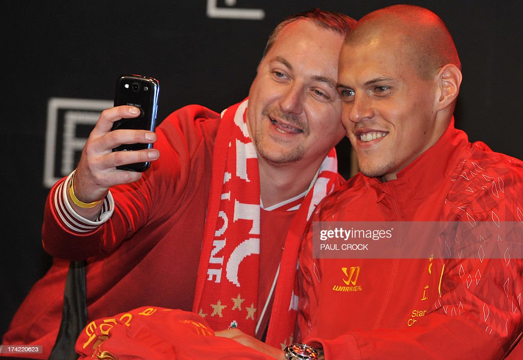 Liverpool FC defender Martin Skrtel (R) poses for a photograph with a fan at Federation Square in Melbourne on July 22, 2013. LIverpool FC will play the Melbourne Victory in front of a near sell-out 90,000 fans at the MCG on July 24. AFP PHOTO / Paul CROCK