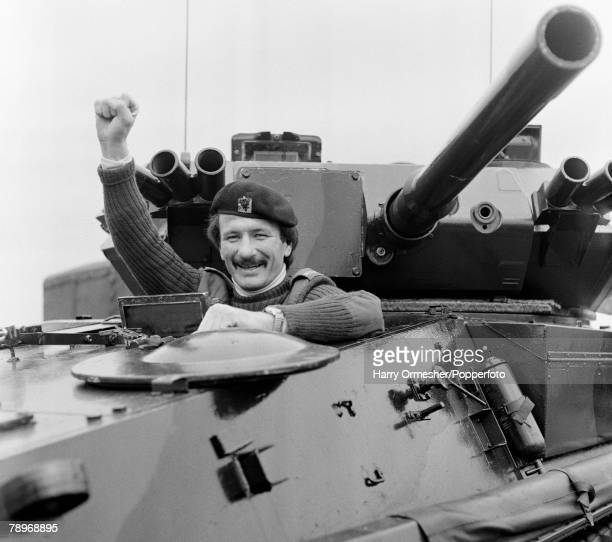 Liverpool FC footballer Tommy Smith posing in army uniform on board a tank on May 10, 1977 in Liverpool, England.