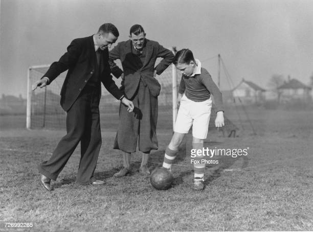 Liverpool FC player Matt Busby giving young player Len Langford some tips as Len's father Manchester City goalkeeper Sam Langford looks on 5th April...