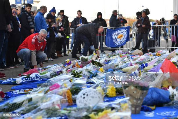A Liverpool football club supporter adds to flowers to a growing pile of tributes outside Leicester City Football Club's King Power Stadium in...