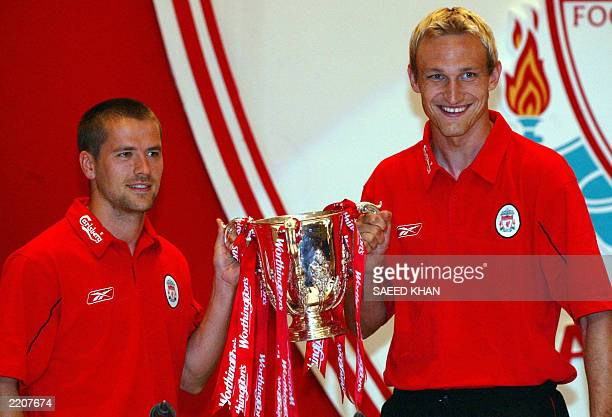 Liverpool football players Sami Hyypia and Michael Owen arrive at a press conference while holding their last trophy in Bangkok 22 July 2003 The...