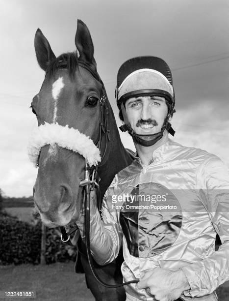 Liverpool footballer David Johnson poses with his racehorse in his jockey silks, circa November 1980.