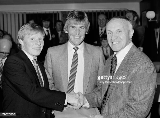 Liverpool footballer Sammy Lee receives a man of the match award from former Liverpool manager Bill Shankly as captain Kenny Dalglish joins them at...