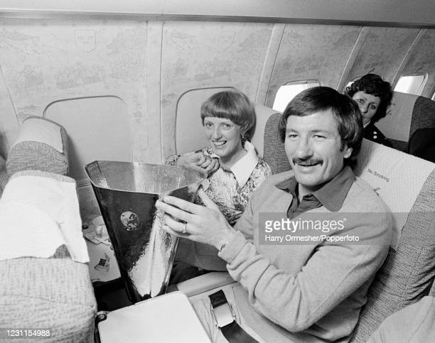 Liverpool footballer Tommy Smith and his wife Susanne celebrate with the damaged UEFA Cup trophy while on the aeroplane heading back to Liverpool,...