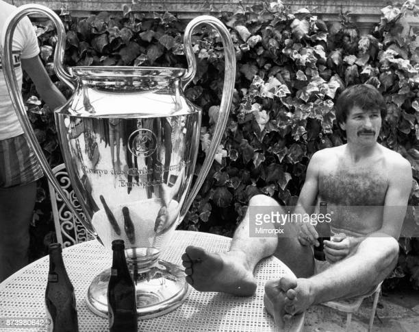 Liverpool footballer Tonny Smith enjoys a bottle of beer as he sits with the famous European Cup trophy following his side's historic victory over...