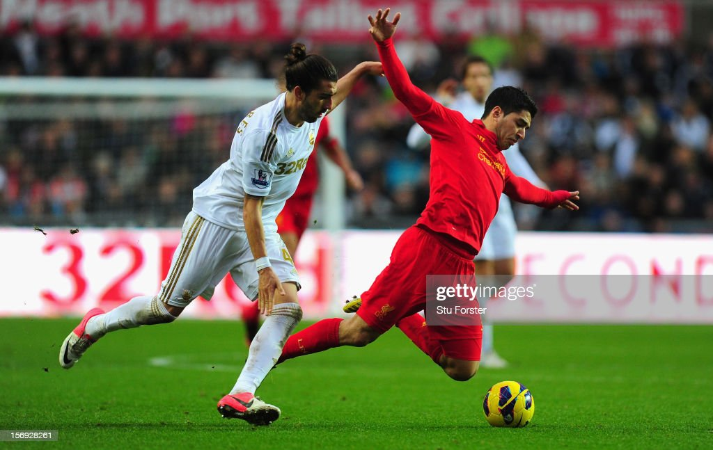 Liverpool forward Luis Suarez (r) is brought down by Swansea defender Chico Flores during the Barclays Premier League match between Swansea City and Liverpool at Liberty Stadium on November 25, 2012 in Swansea, Wales.