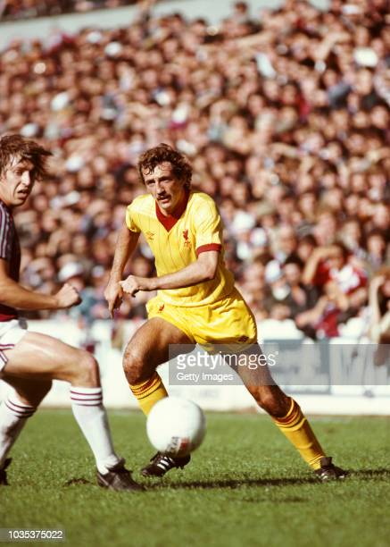 Liverpool fullback Alan Kennedy wearing the yellow with red pinstripe Umbro away kit plays the ball past West Ham player Geoff Pike during a First...