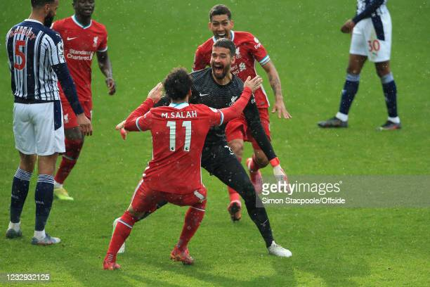 Liverpool goalkeeper Alisson Becker celebrates scoring a last minute goal with Mohamed Salah and Roberto Firmino during the Premier League match...