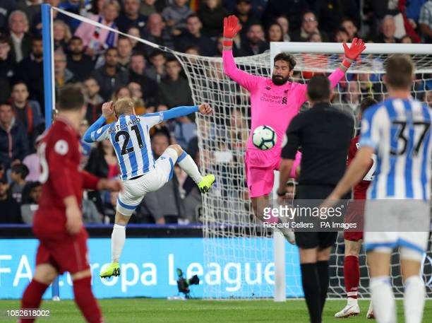 Liverpool goalkeeper Alisson Becker makes a save from Huddersfield Town's Alex Pritchard during the Premier League match at the John Smith's Stadium...